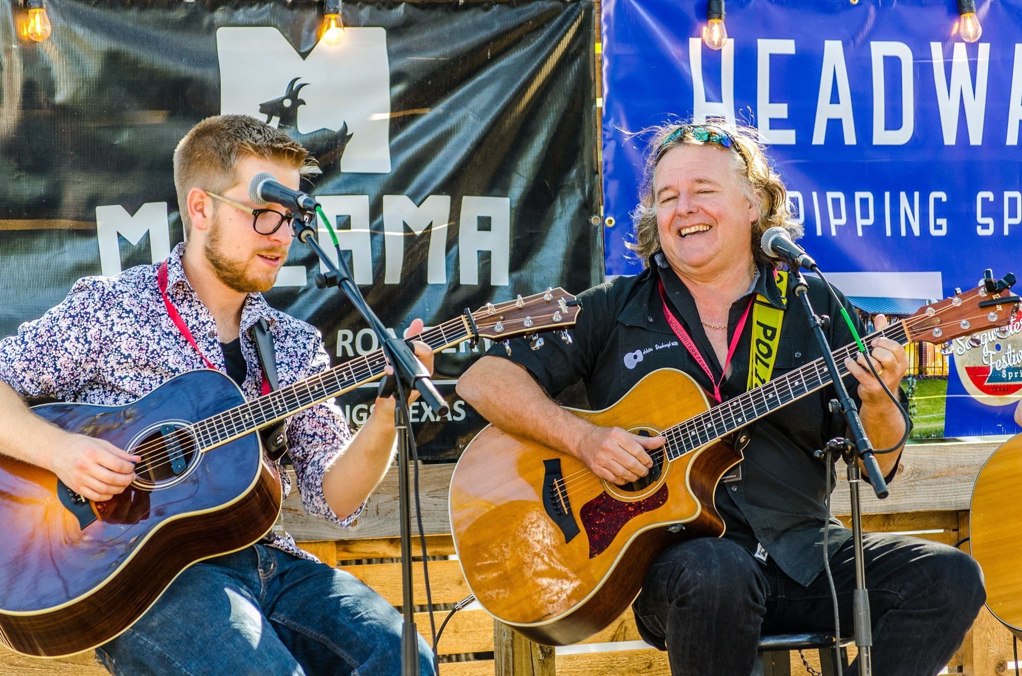 Two smiling songwriters performing,