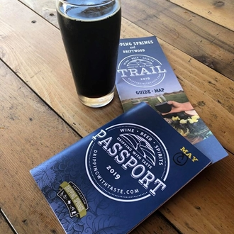 a dark colored beer with two pieces of paper literature on a wooden table