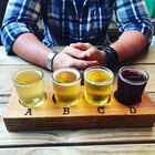 a tasting flight of four different beers with a person's hand crossed on a wood table.