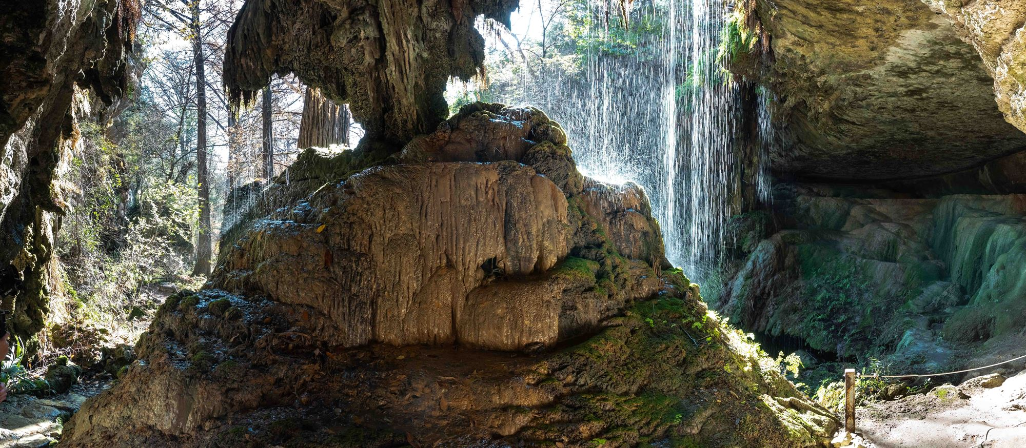 a panoramic image of a waterfall dripping on a stone