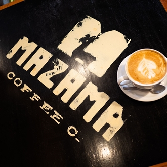 A picture of a latte on a table that says Mazama