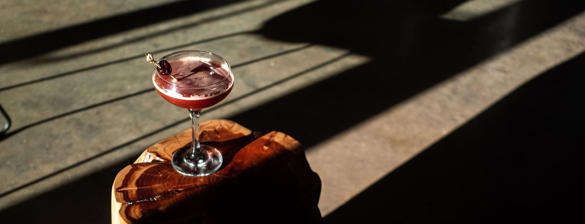A dark red cocktail setting on a wooden stool