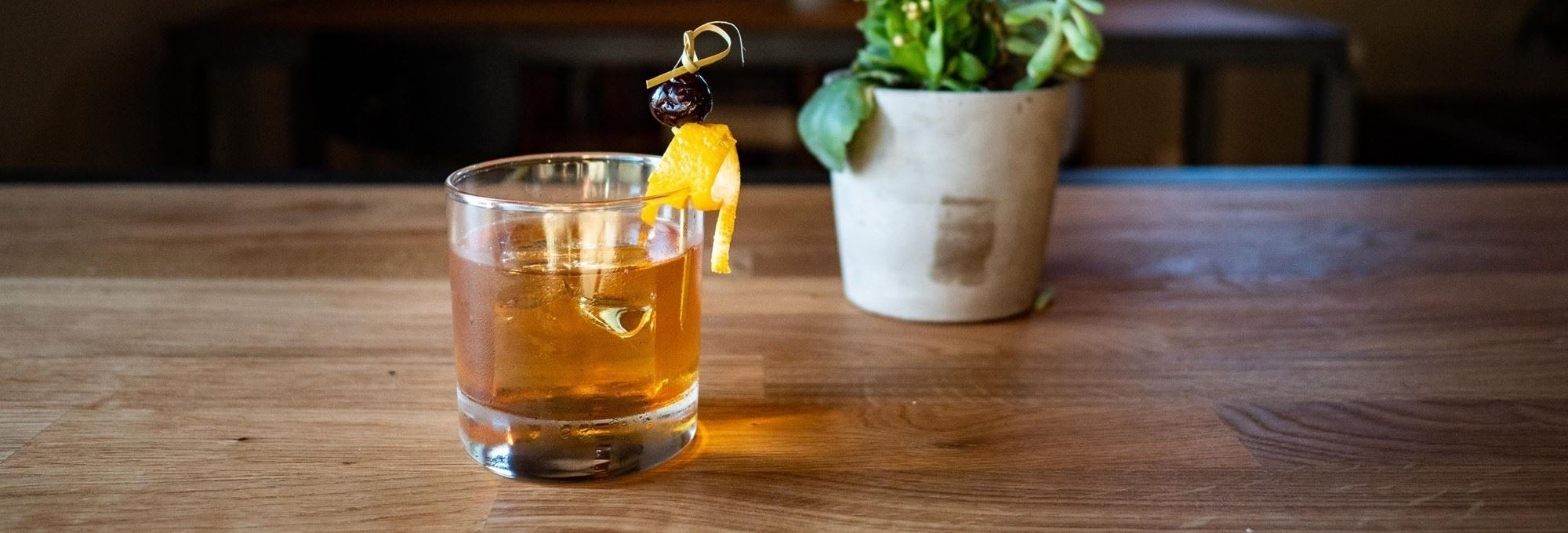 an Old Fashion cocktail with an orange peel and cherry as garnish with a plant in the back ground atop a wooden bar