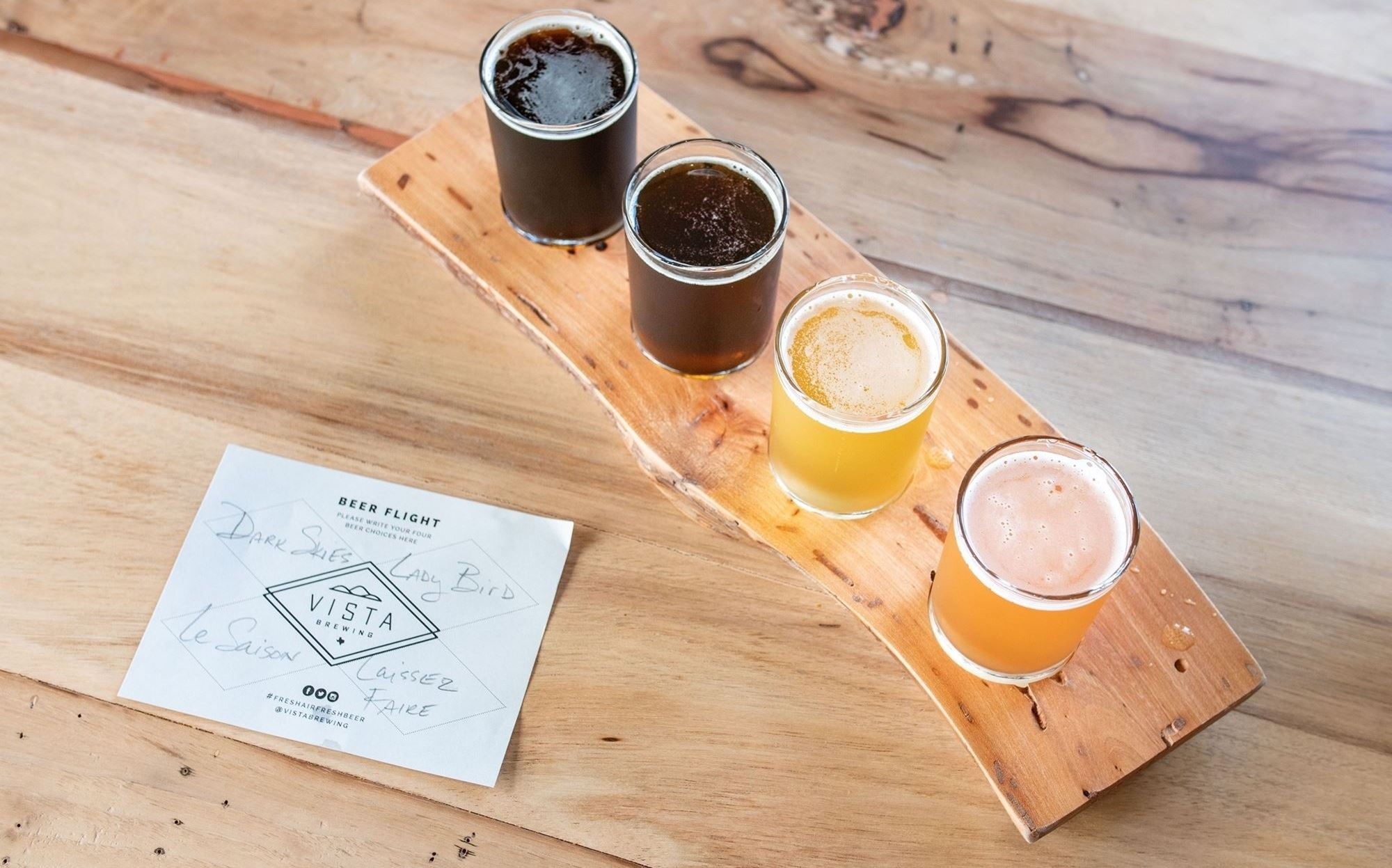 A flight of beer on a wood table