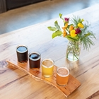 A flight of beers sitting on a table near a vase of flowers