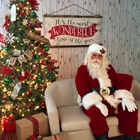 Santa Claus sitting on a couch next to a decorated Christmas tree