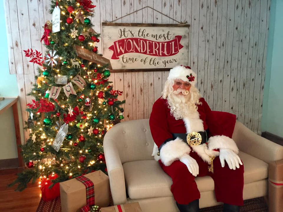 Santa Claus sitting on a sofa near a Christmas tree