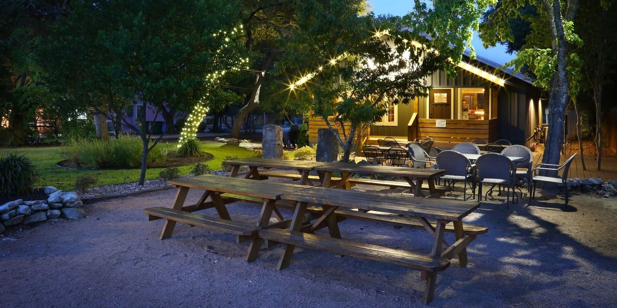 The front of a small building at night with string lights illuminating picnic tables and the front porch