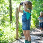 A young girl in overalls in the woods peering out of binoculars