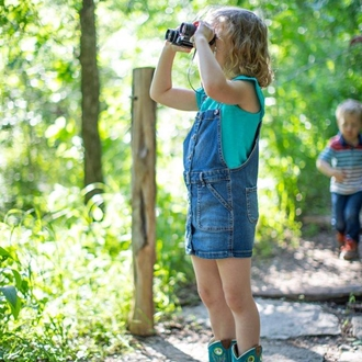 a little girl on a dirt path looking through binoculars in the woods