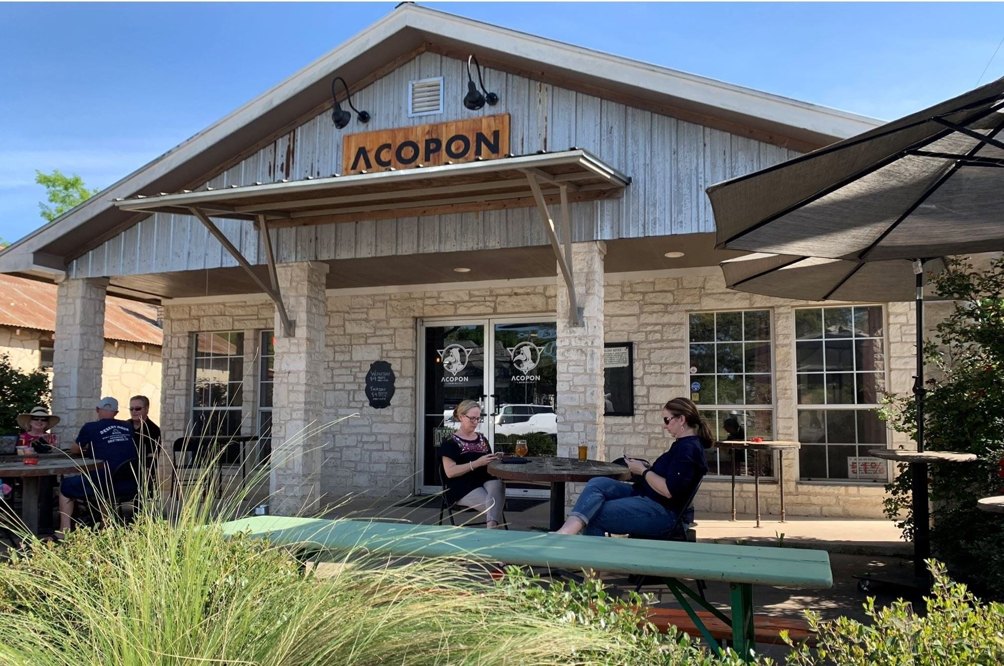 The front of Acopon brewing with a front porch with two women sitting on picnic tables enjoying a beer