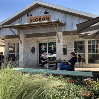 the front of a brewery with picnic tables and two women sitting at the picnic tables