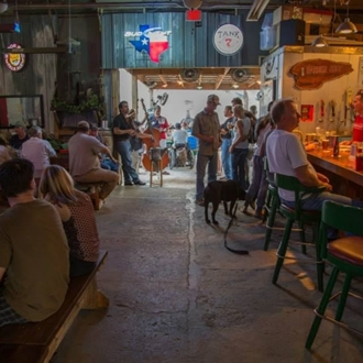 An interior shot of the barbershop bar where people are gathered around picnic tables and the bar