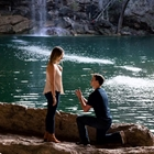 A man on one knee proposing to a woman in front of a waterfall
