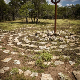 A metal art installation surround by rocks laid on the ground in a centric formation