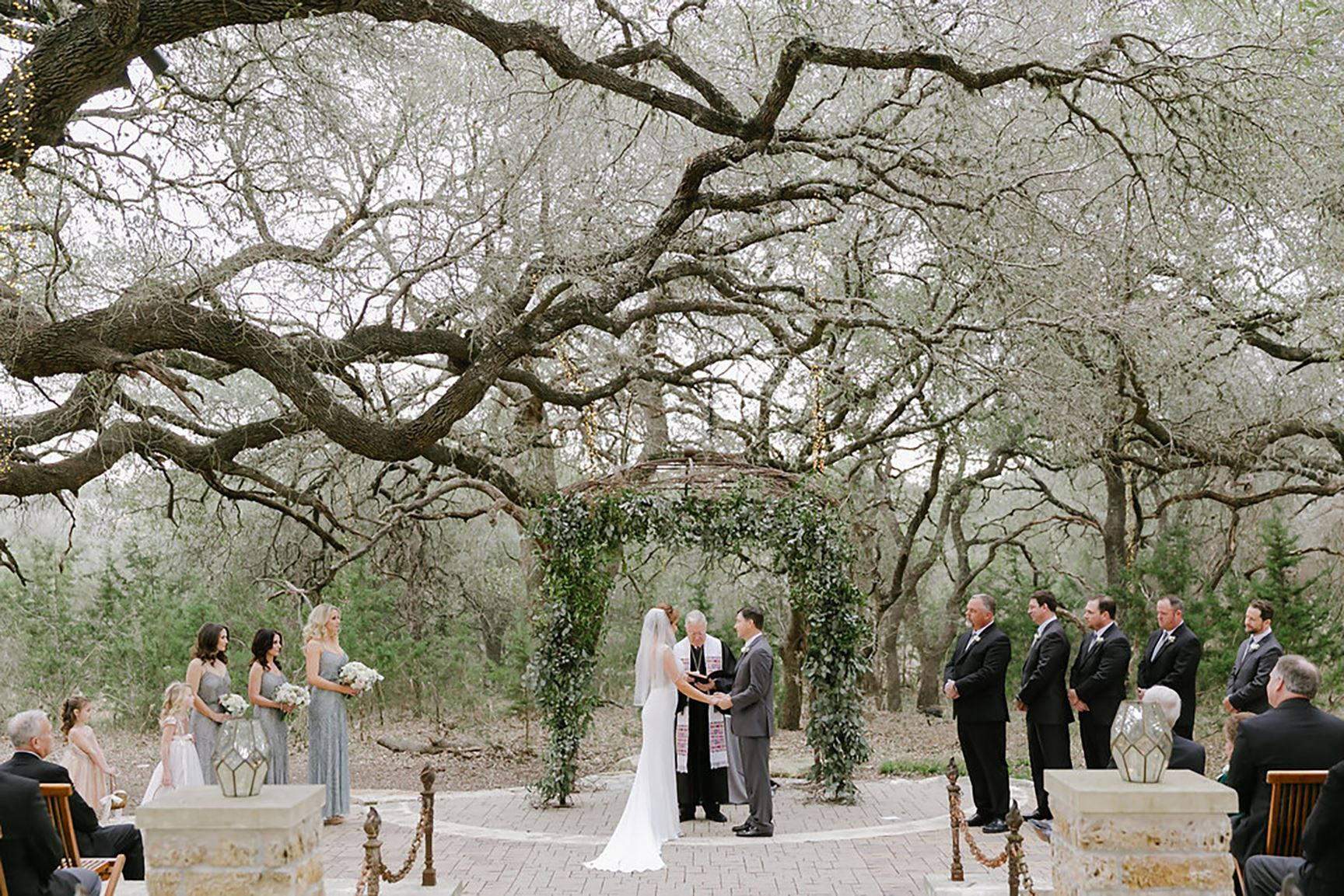 A man and a woman with a bridal party getting married underneath an oak tree in an outdoor ceremony