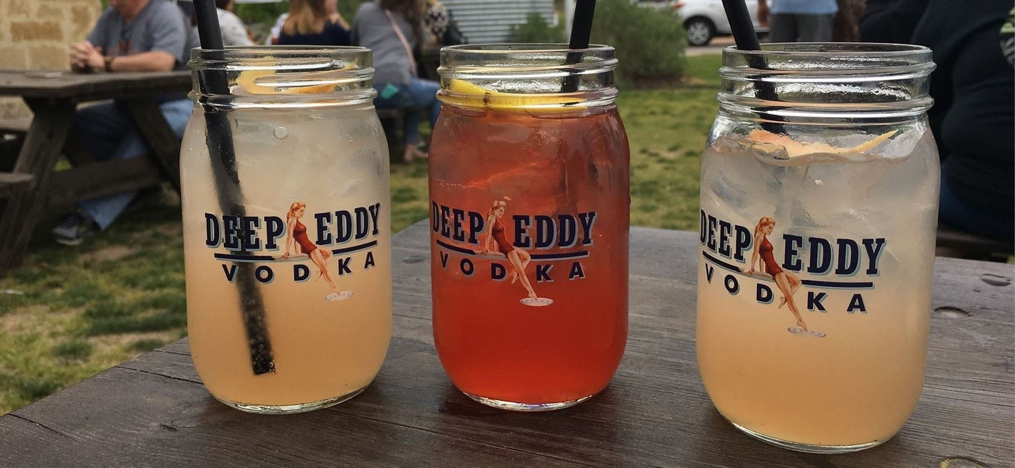 three mason jars with cocktails in each of them outside.