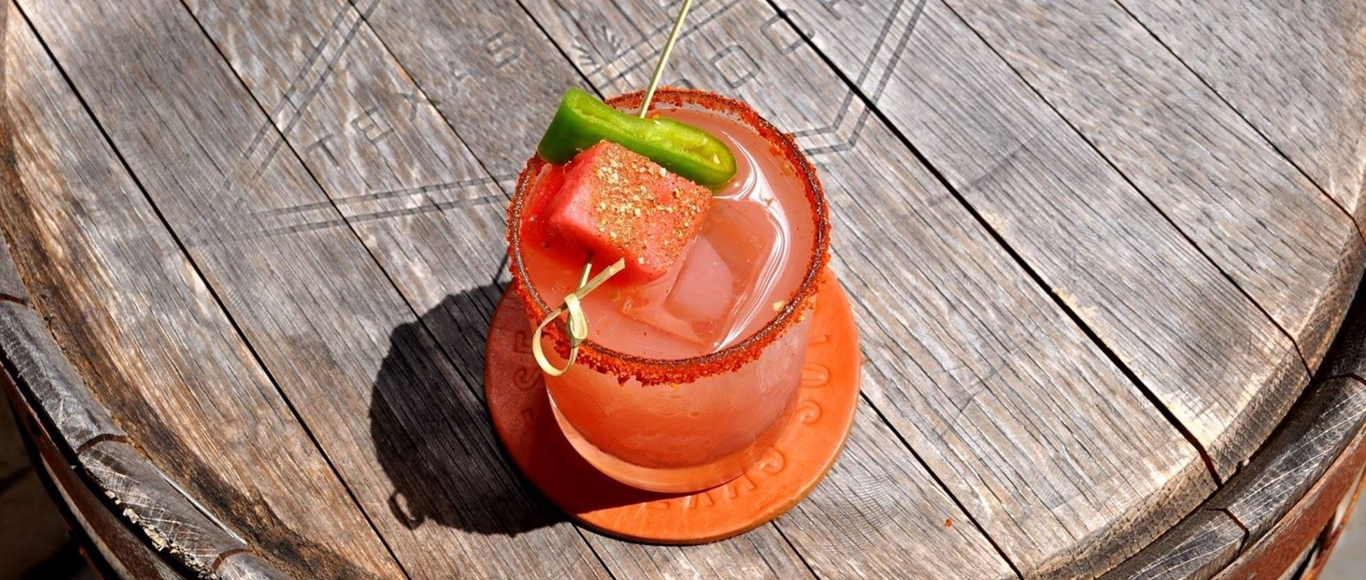 A cocktail with a salted rim and a watermelon and jalapeno as garnish on a wooden barrell