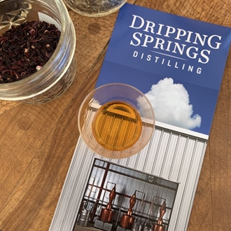a small glass of whiskey sitting on a Dripping Springs Distilling pamphlet