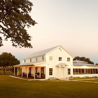 A two story white wedding ceremony barn