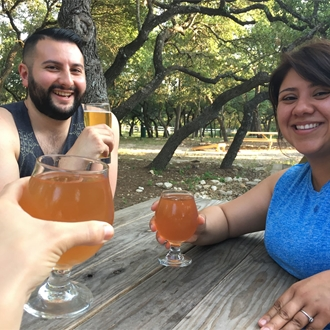 a smiling couple holding beers outdoors