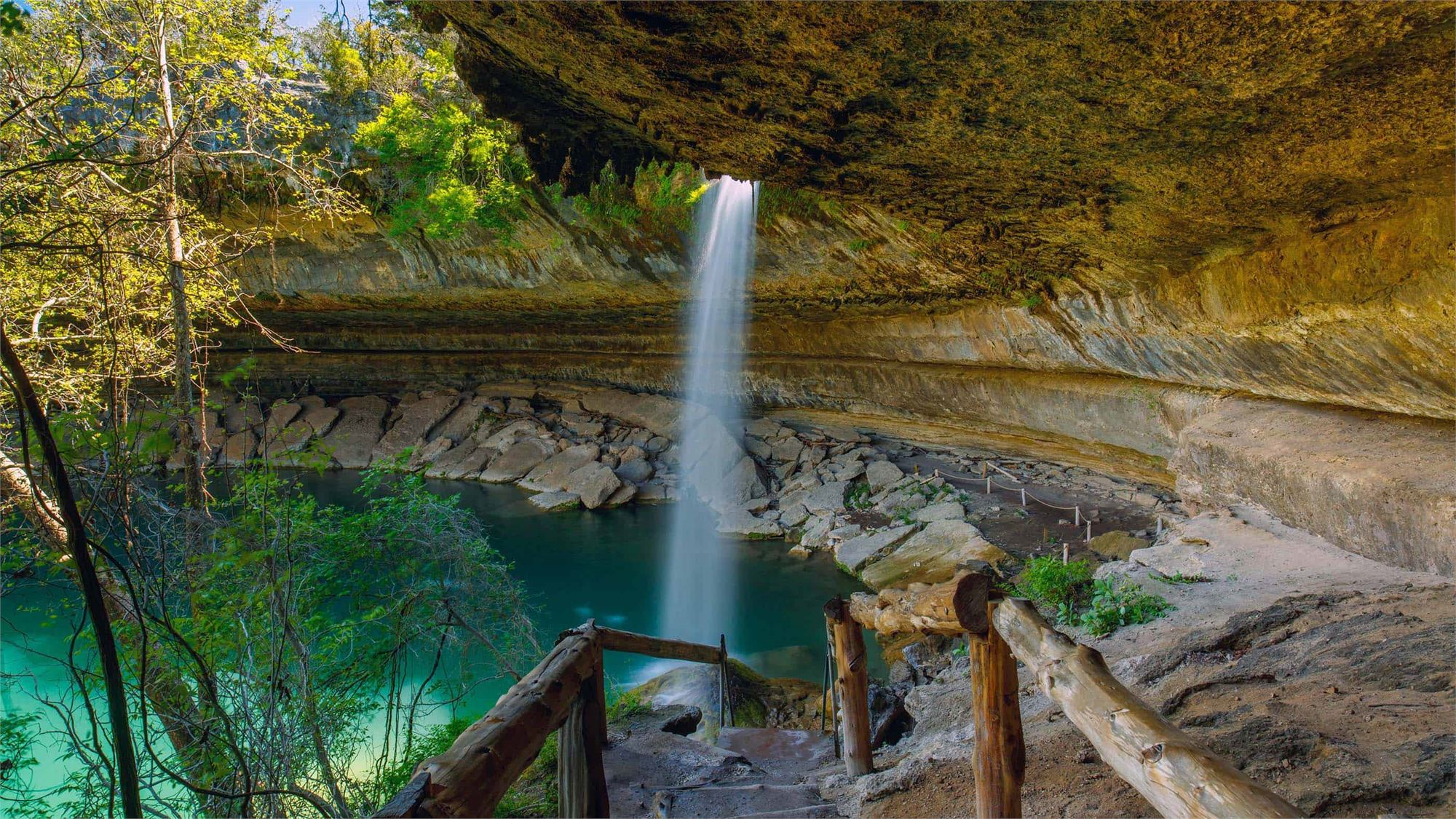 A waterfall falling into a big natural pool
