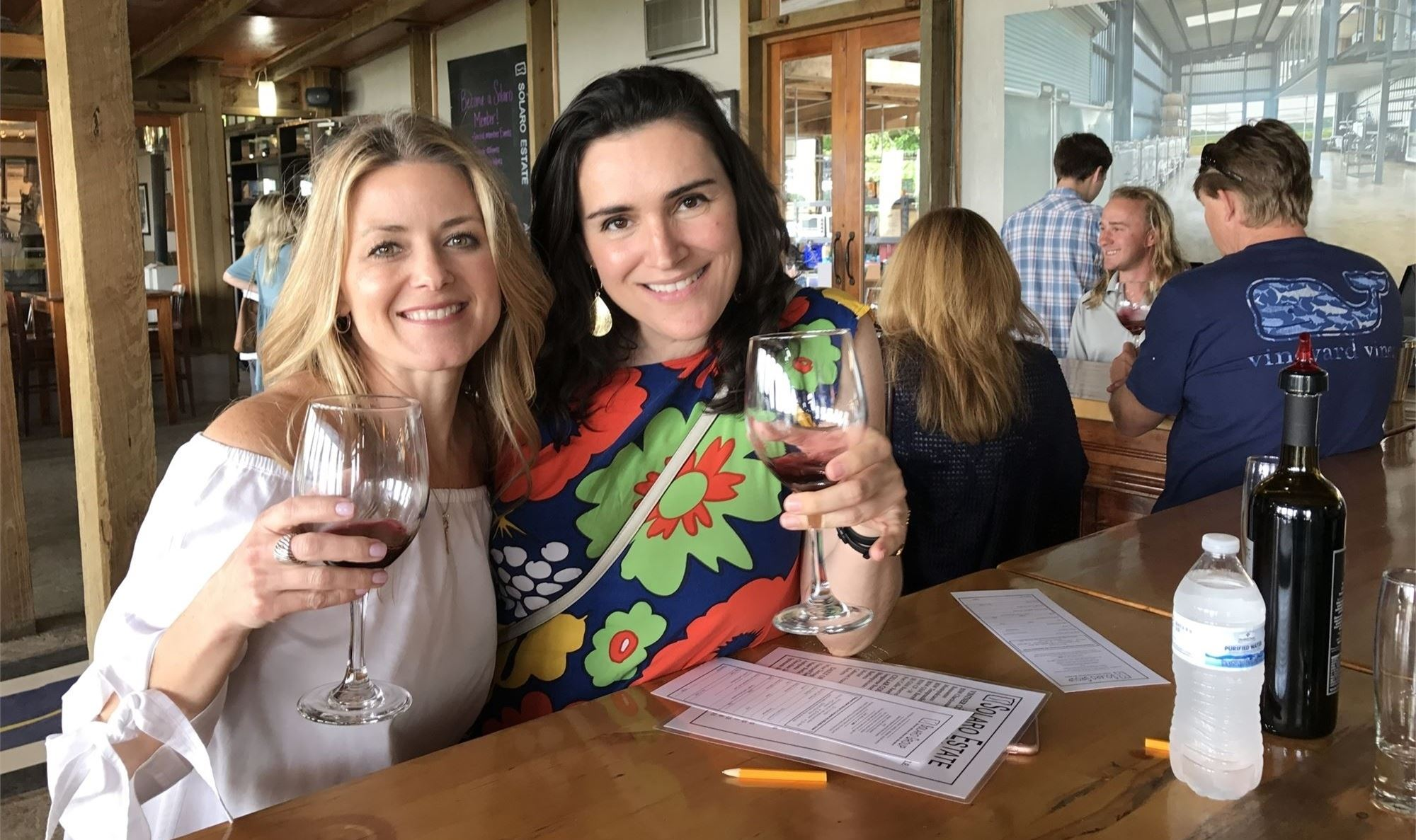 Two women holding glasses of red wine in a wine tasting room