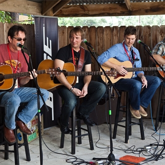 4 musicians with guitars sitting on stools with one musician strumming his guitar