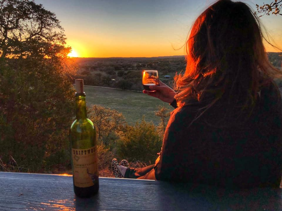 a woman looking at a sunset holding a glass of wine in her right hand