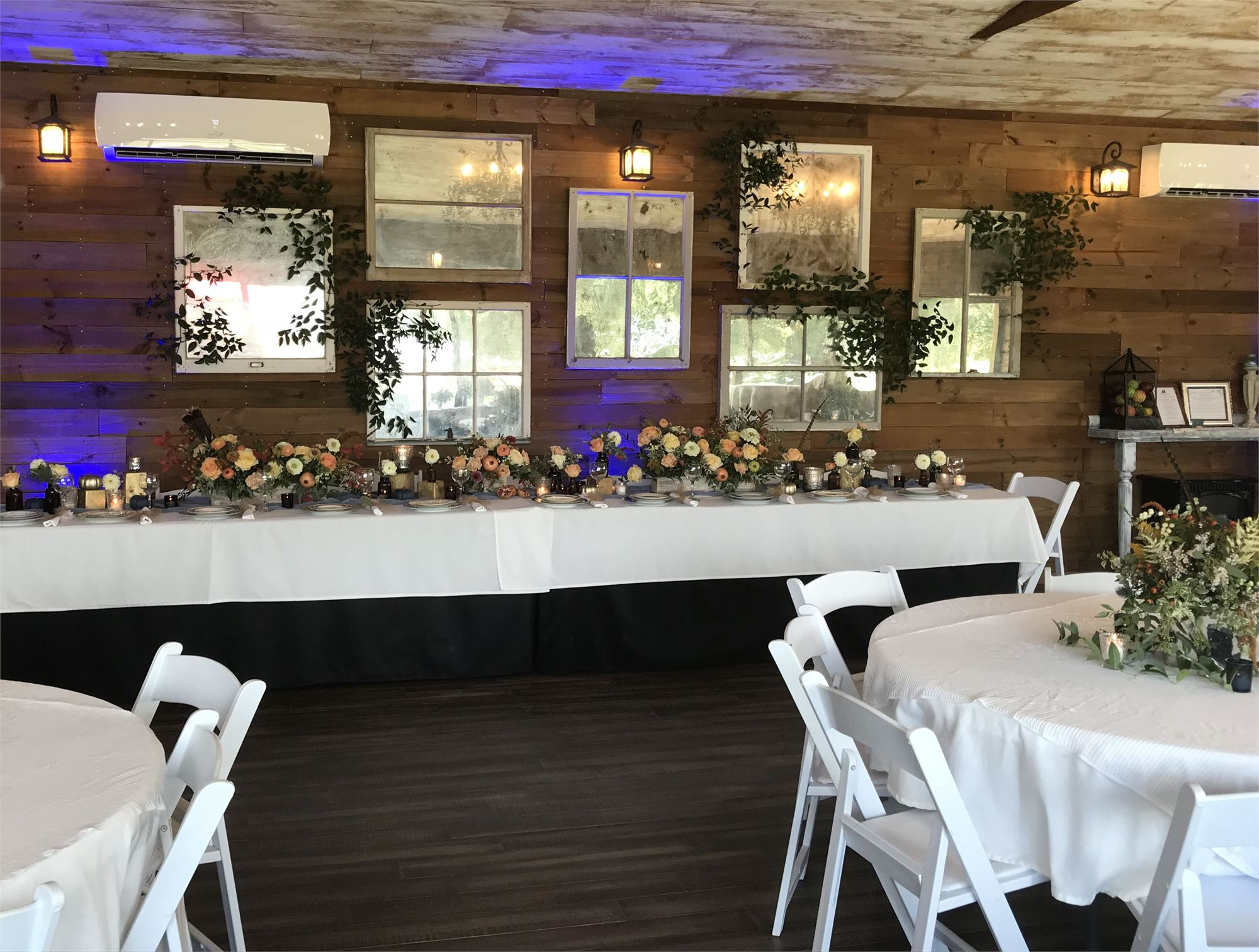 A banquet hall set up with florals on a long table.