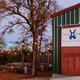 A picture of Last Stand Brewery taproom and the courtyard with trees strung with twinkle lights.