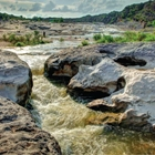 The Pedernales River running in between rocks.