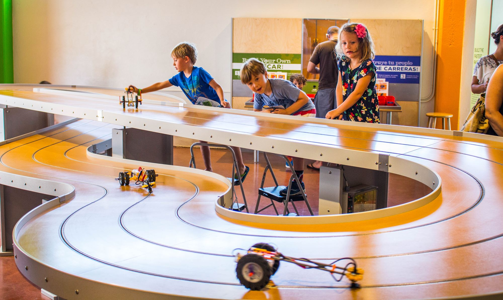 Children playing with a racetrack inside a museum.