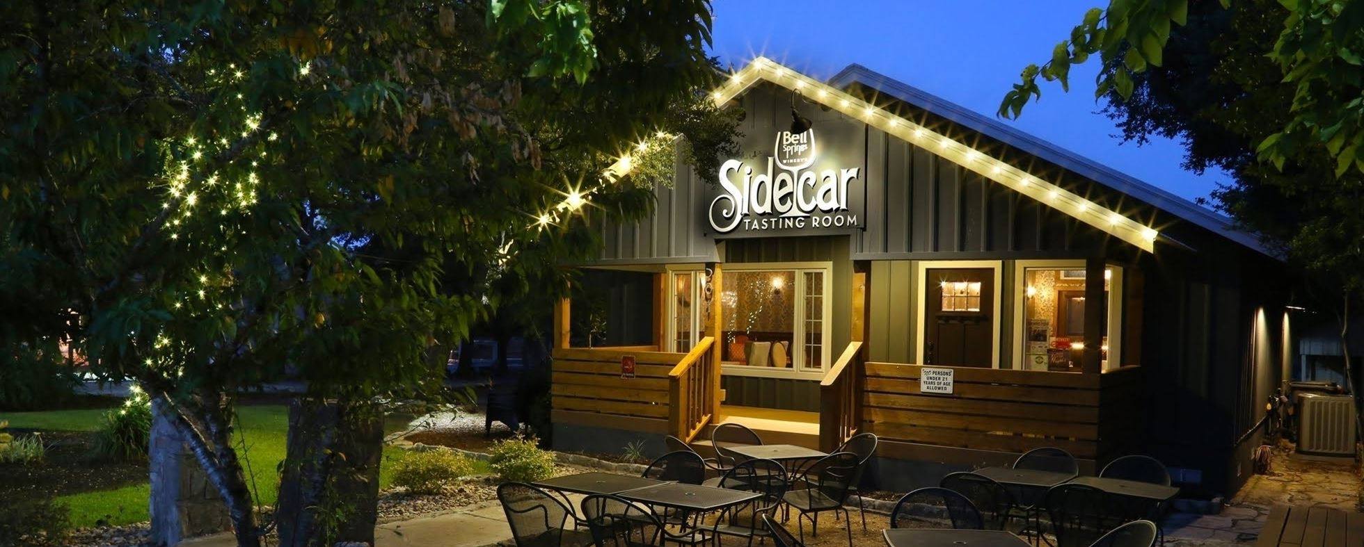 The outside of Sidecar Tasting Room at dusk.