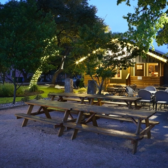 The outside of the tasting room with picnic tables and a small porch.
