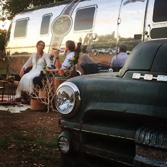 A couple enjoy a cigar outside a vintage airstream trailer.