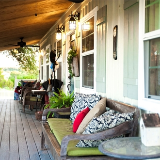The front porch of a cabin with benches for sitting.