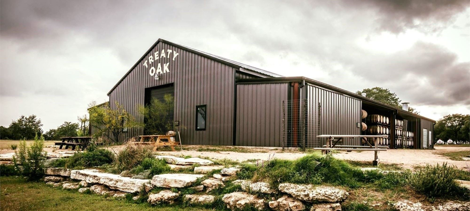 A grey metal building with the words Treat Oak on the front above the garage door