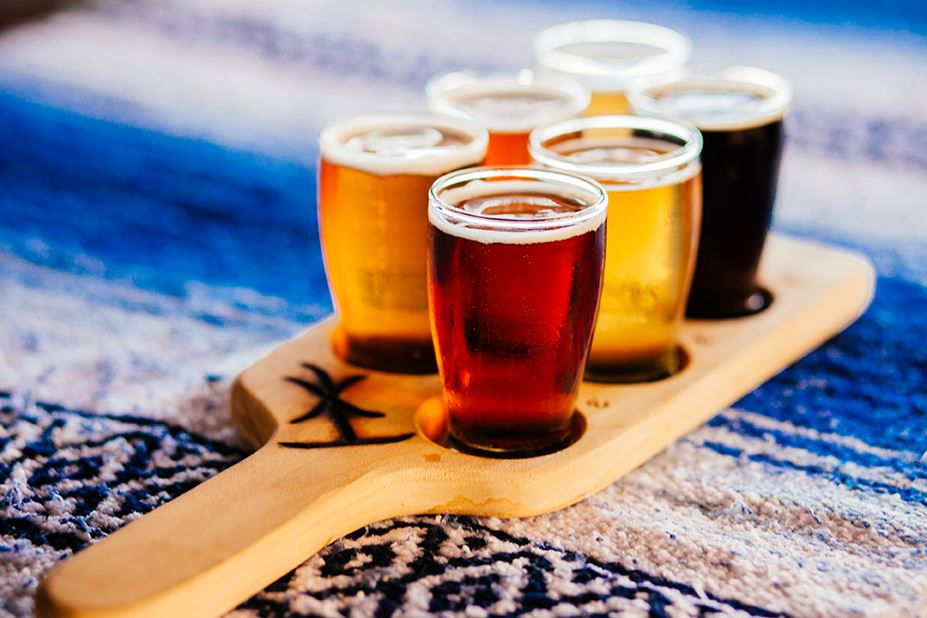 A flight of six beers on a tasting paddle on a blue blanket