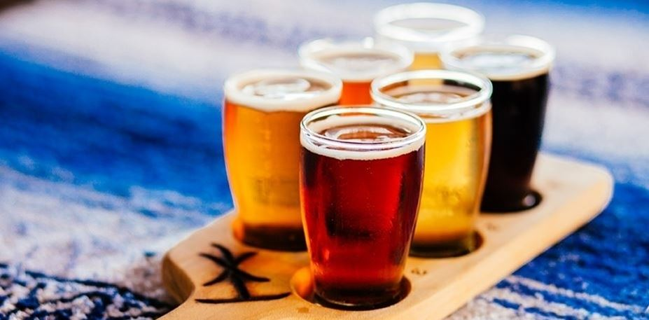 A flight of 6 different kinds of beer on a wooden paddle