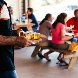 A person carrying a flight of beer on a covered patio.