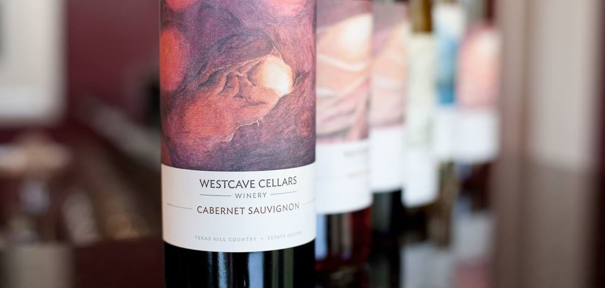 a line of wine bottles from Westcave Cellars