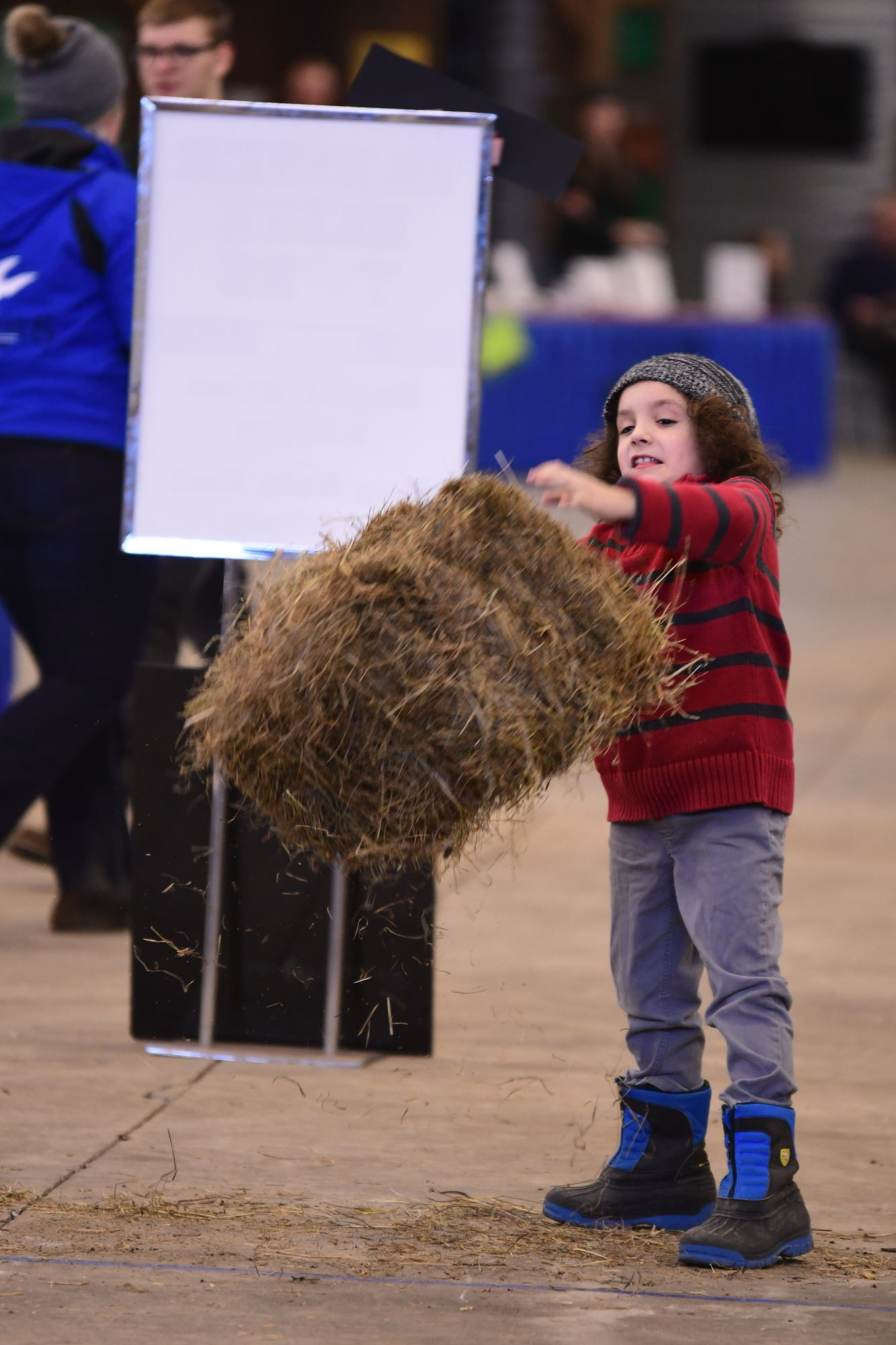 Child throwing Hay Bale