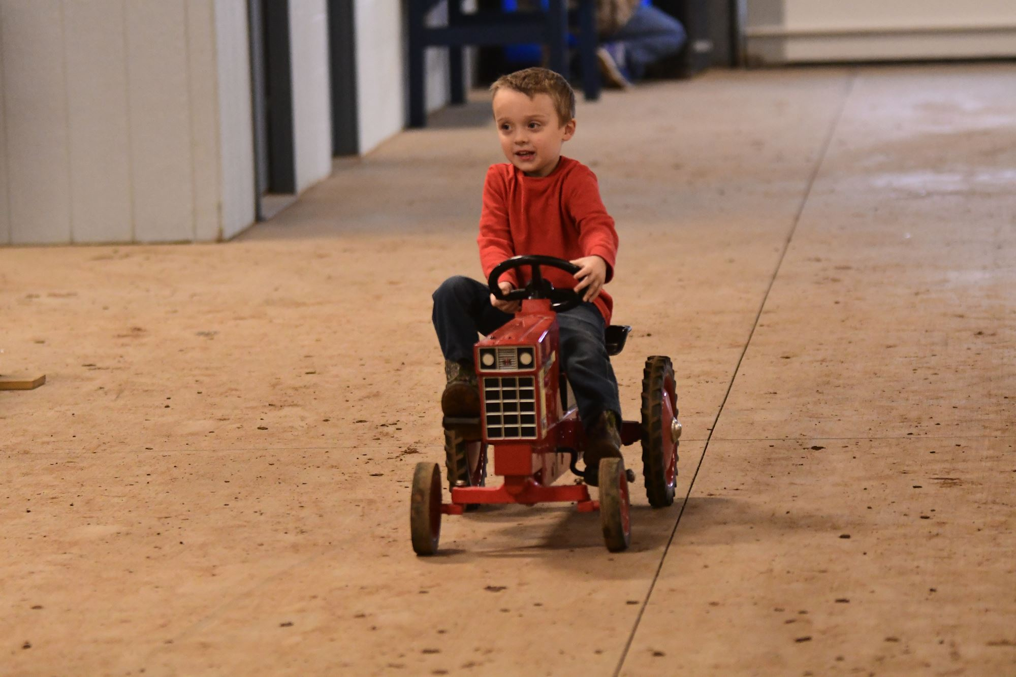 Child riding a pedal tractor