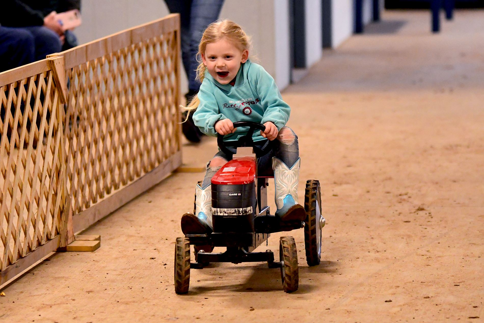 Girl riding on a pedal tractor