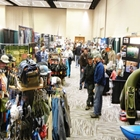 Multiple persons move between booths. The booths contain fishing related products.