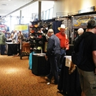 Persons look at different booths. Booths contain fly fishing apparel.