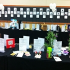 Two rows of tables have different types of cards placed on them. White balloons are in the background