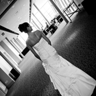 A bride faces away from the camera. She is on the upper concourse and the photo is in black and white.