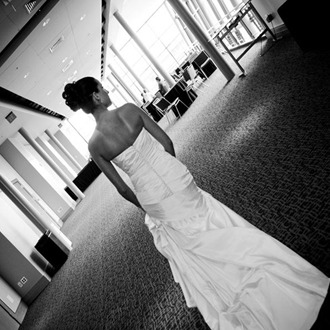 A bride looks away from the camera and she walks along the upper hallway. The room in brightly lit with tall windows.